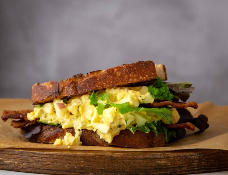 Egg Salad on Sourdough with green lettuce on a wooden board