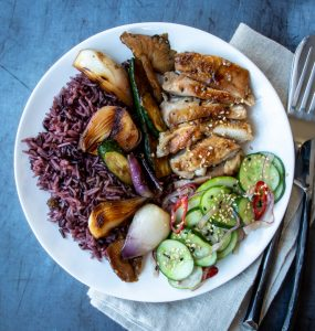 Grilled chicken, rice, and cucumber salad on a white plate