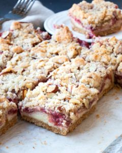 A plate of cookie bars filled with cheesecake and strawberry rhubarb.