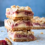 A stack of cookie bars with cheesecake and strawberry rhubarb filling