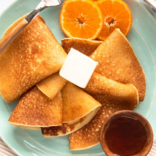 A plate of Swedish pancakes, butter, syrup and orange slices