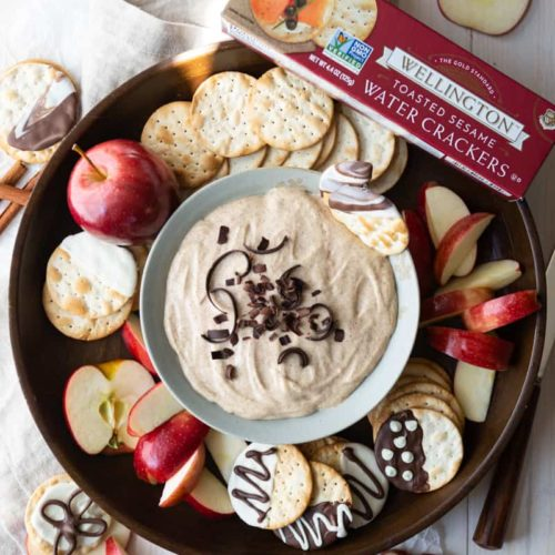 a platter of cinnamon churro dip with crackers and apples