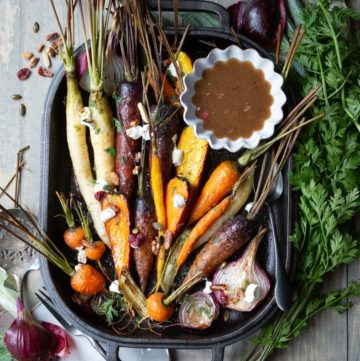 roasted carrots on cast iron pan with vinaigrette