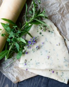 Easy Herb Pie Crust - folded pie crust on a table with herbs and a rolling pin.