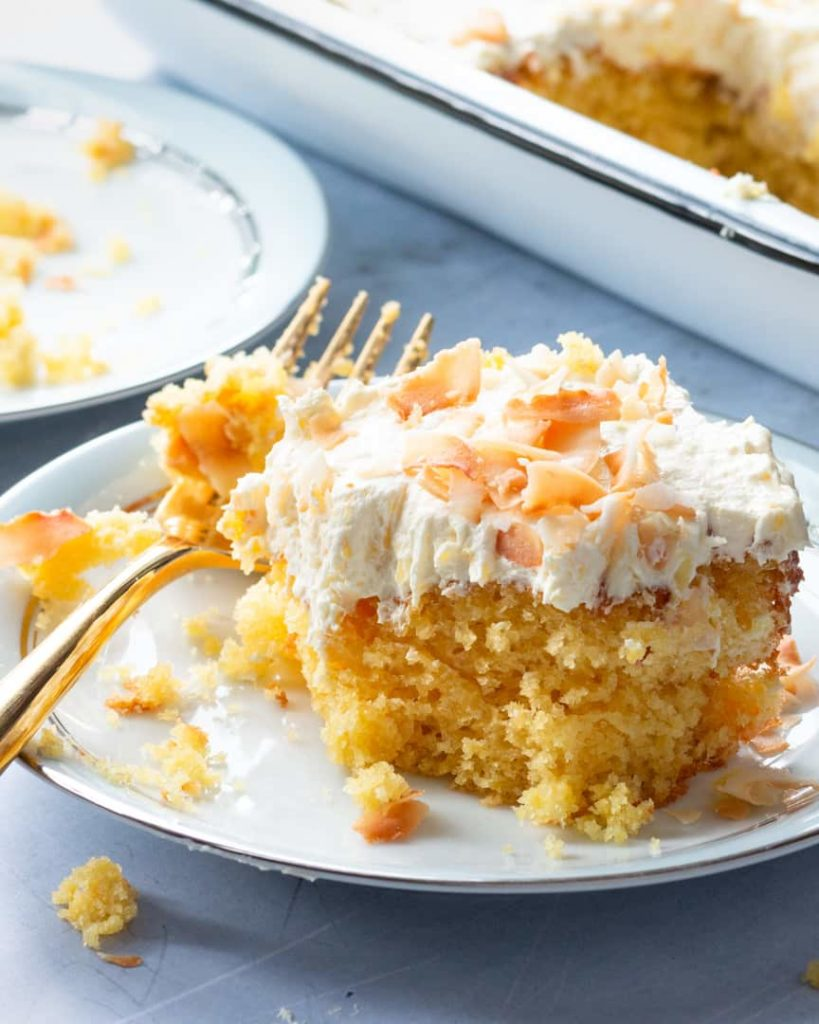 A piece of pineapple cake with light frosting and toasted coconut.