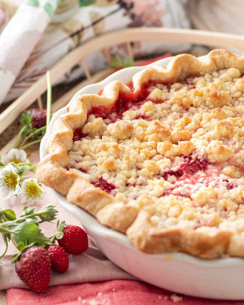 A strawberry rhubarb pie with a slice cut out on a basket and strawberry leaves and flowers.