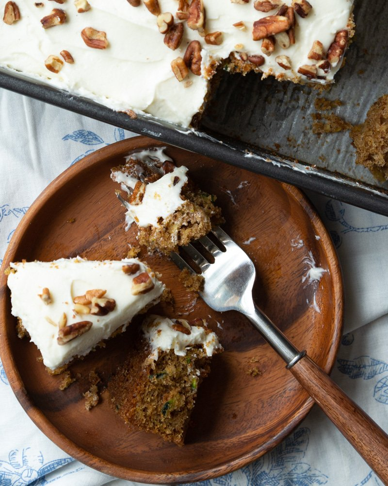 A slice of Zucchini Spice Cake with Cream Cheese Frosting on a plate with the cake pan in the background.