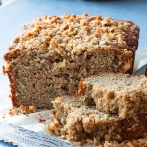 A loaf of zucchini applesauce bread with brown sugar oat streusel that is sliced.