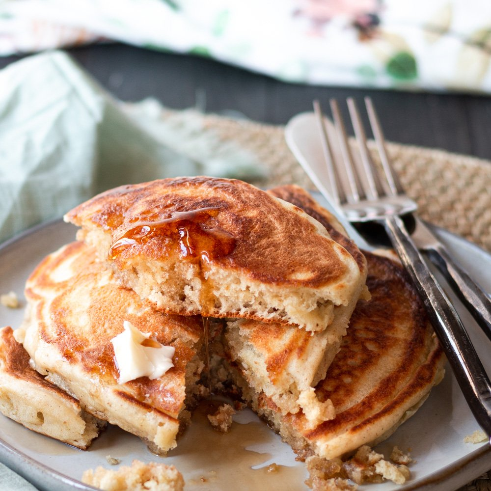 a stack of pancakes on a plate with butter and syrup