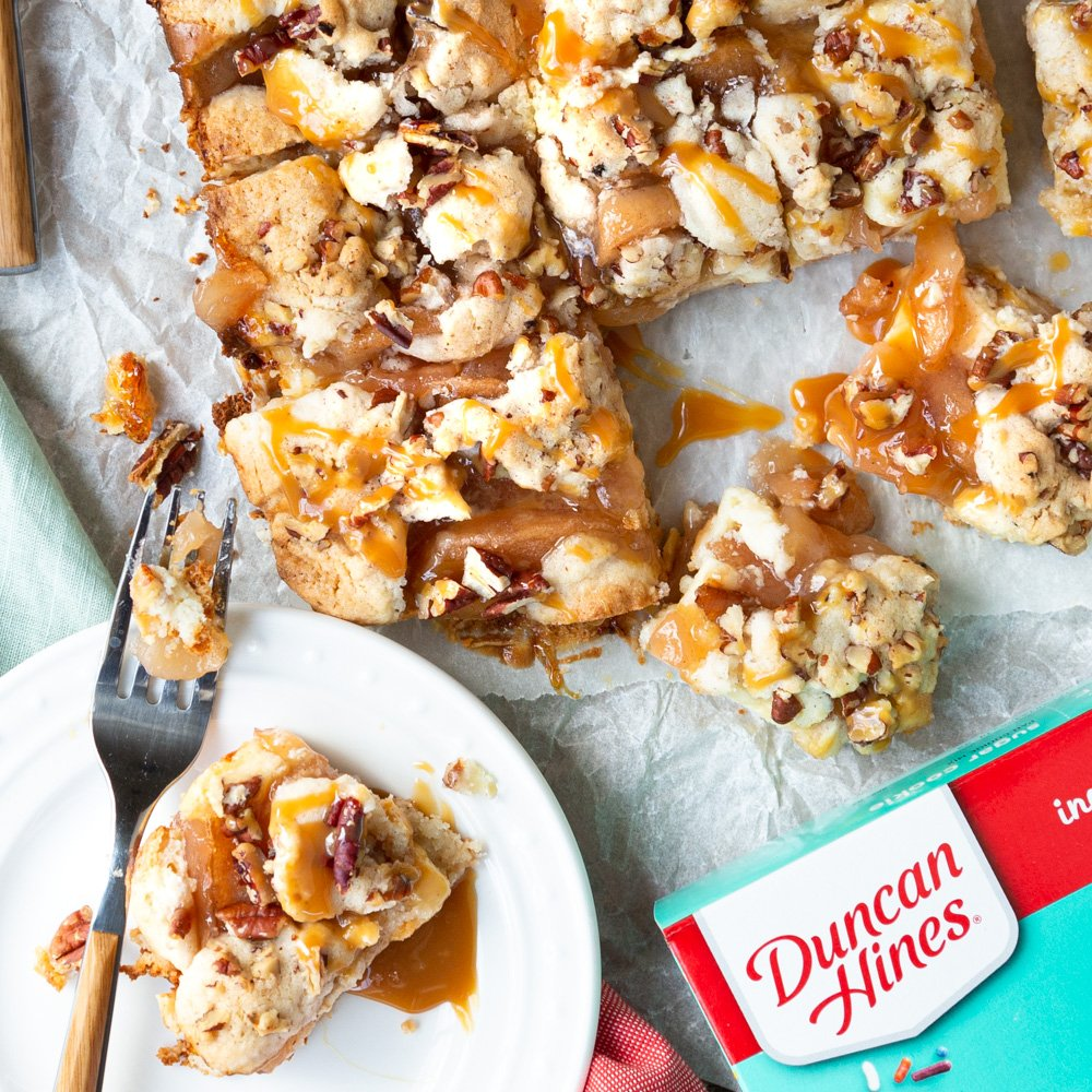 A tray of Duncan Hines Gooey Caramel Apple Cheesecake Cookie Bars cut into squares with a serving plate and the box of Duncan Hines Cookie mix in the corner.