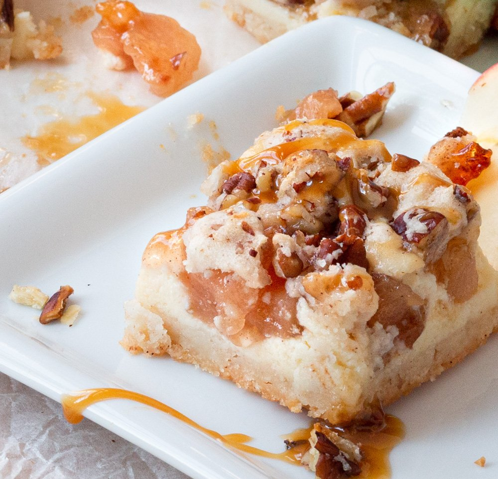 A serving of Duncan Hines Gooey Caramel Apple Cheesecake Cookie Bars on a place, with caramel sauce and pecans.