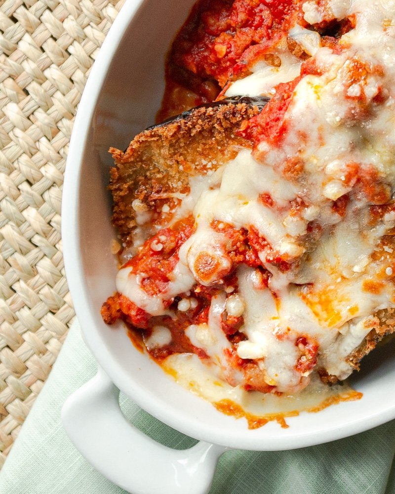 Restaurant Style Eggplant Parmesan in an oval baking dish. Topped with marinara sauce and bubbly golden brown cheese.