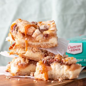 A stack of Duncan Hines Gooey Caramel Apple Cheesecake Cookie Bars with parchment paper in between, placed on a cutting board.