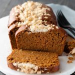 A loaf of Pumpkin Spice bread with Streusel Topping sliced and on a serving tray.