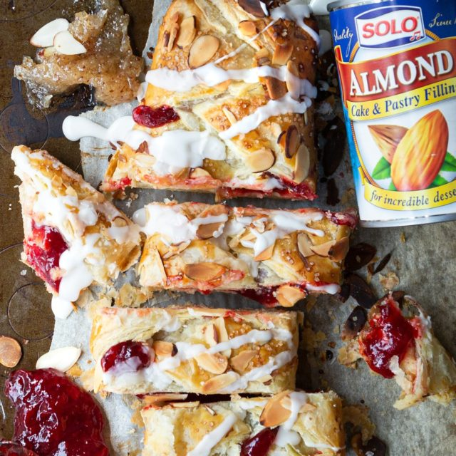 Sliced strudel with frosting on a baking sheet with parchment paper and a can of Color Almond Cake & Pastry Filling next to it.