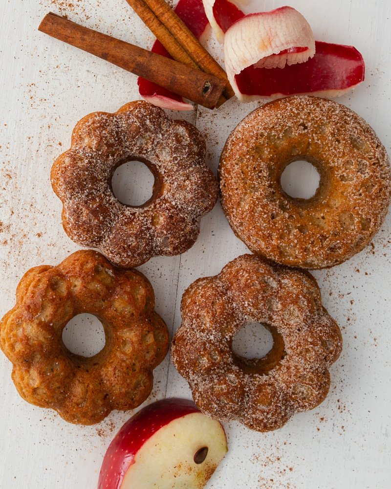 4 little apple cider donuts on a wooden board make with Duncan Hines cake mix, apples, and cinnamon sticks.