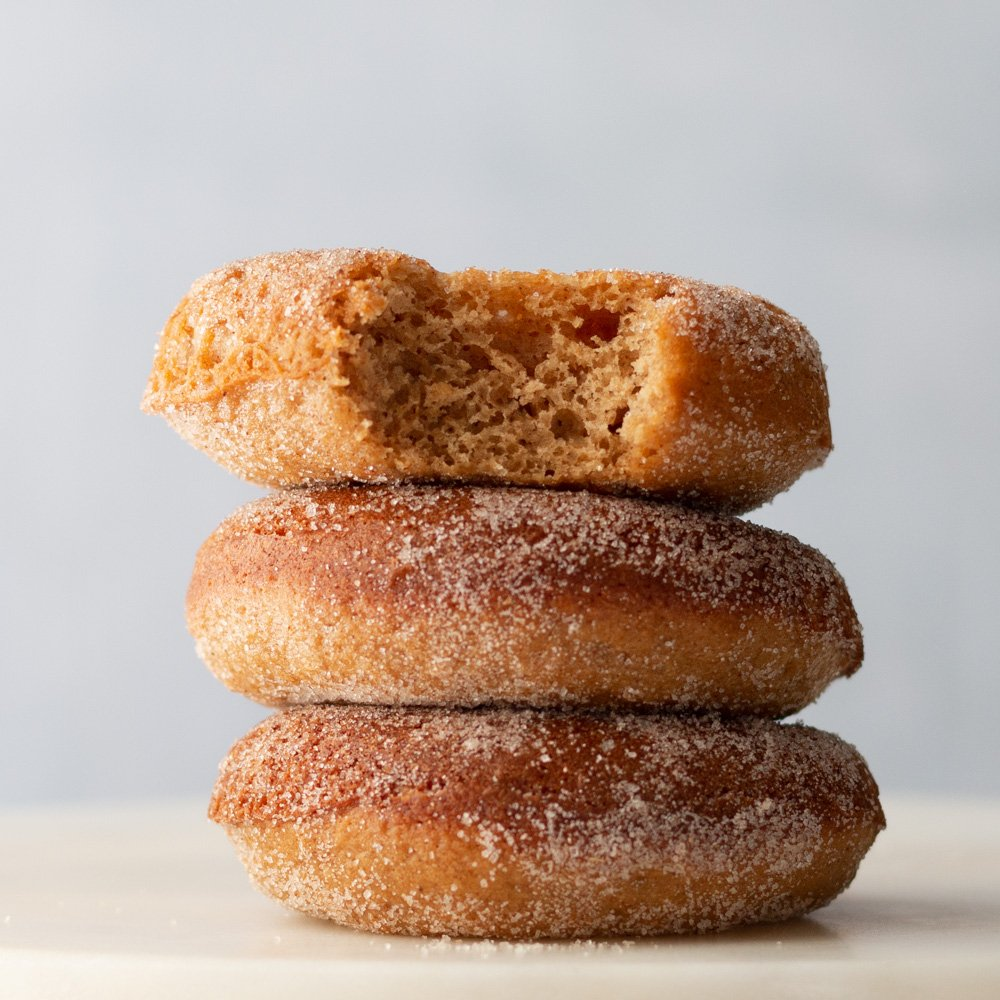 A stack of baked apple cider donuts with a bite taken out of the one on top. image is a straight on view.
