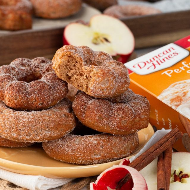 A plate of stacked baked apple cider donuts made with Duncan Hines cake mix.