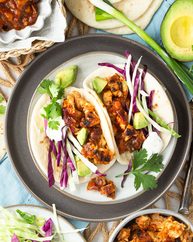 Two chopped chicken tacos on a plate with cabbage, avocado, and crema.