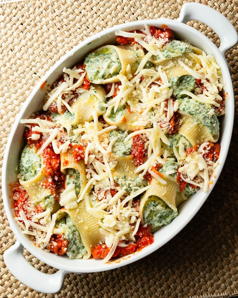 A casserole dish with stuffed shells, pasta sauce, and whipped ricotta. An easy stuffed shell recipe you can use either kale or spinach.