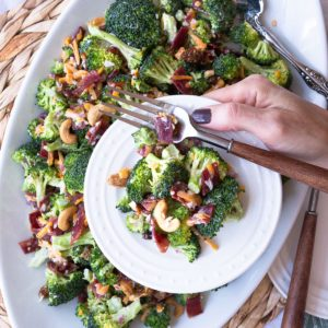A platter of country style broccoli salad. A classic recipe with broccoli, bacon, cheddar, red onion and a creamy dressing.