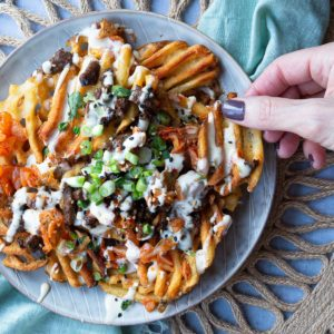A plate of Loaded Korean Kimchi Fries with a hand reaching in a taking some
