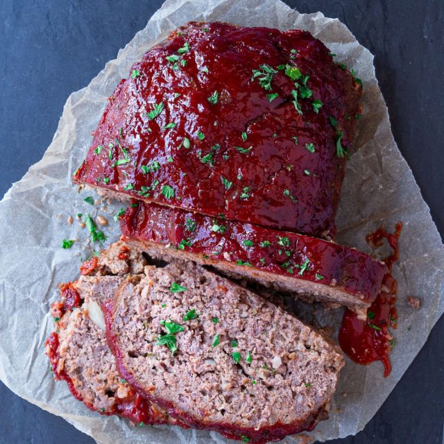 An overhead image of sliced classic meatloaf with a chili sauce glaze.