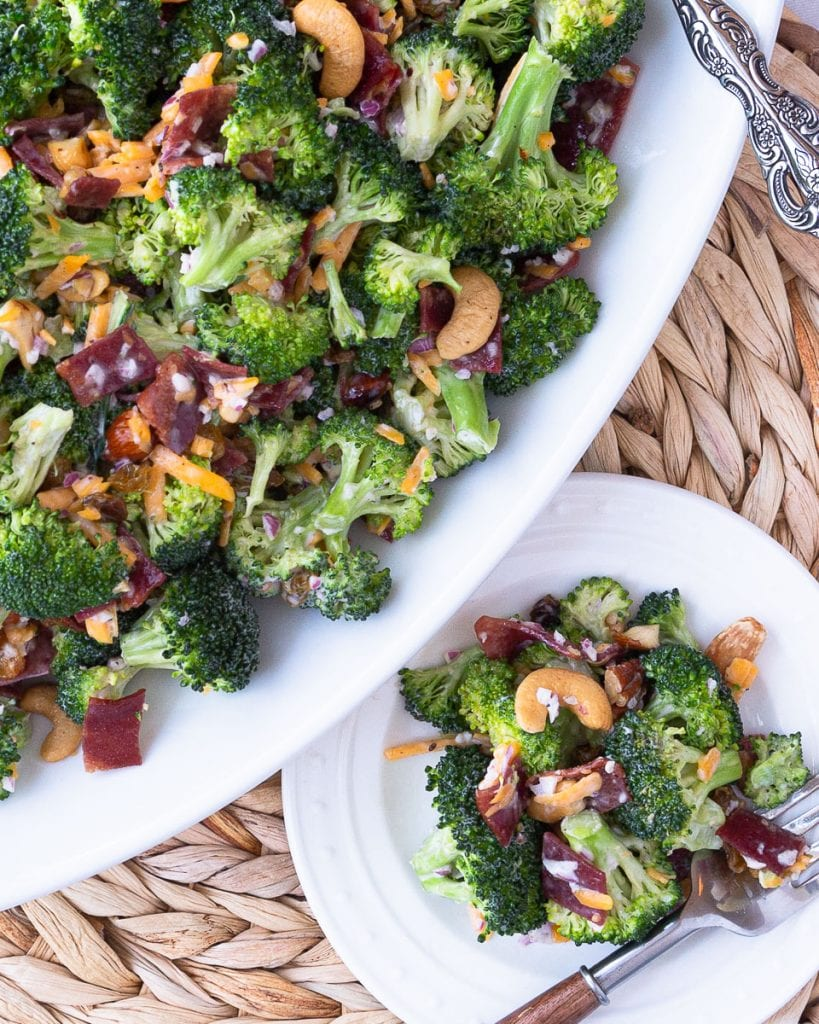 A platter of country style broccoli salad with nuts, bacon, cheddar cheese, red onion, and raisins.