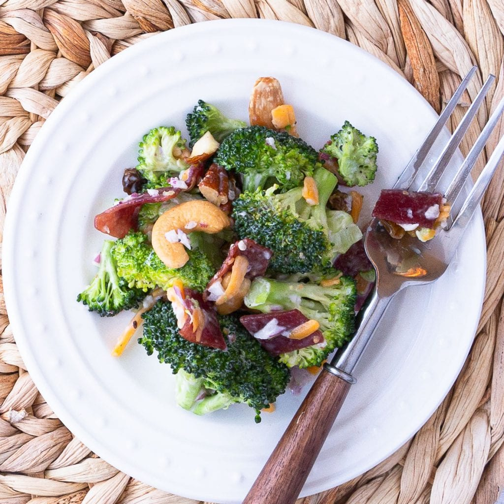 A serving of broccoli salad on a plate with a fork