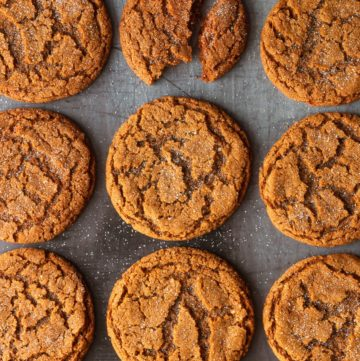 A baking sheet with ginger molasses cookies with one that's got a bite taken out of it.
