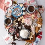 A large round serving tray with Swiss Miss Hot Chocolate, Reddi-wip whipped cream, and Duncan Hines sugar cookies and brownies.