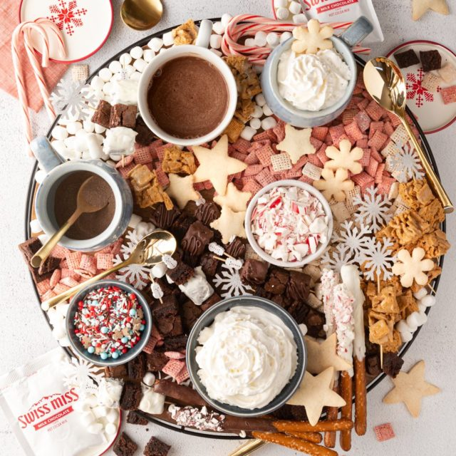 A large round hot chocolate charcuterie board with Swiss miss hot chocolate , whipped cream, and dippers