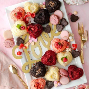 A charcuterie platter of mini heart cakes, red velvet, strawberry, dark chocolate, and raspberry.