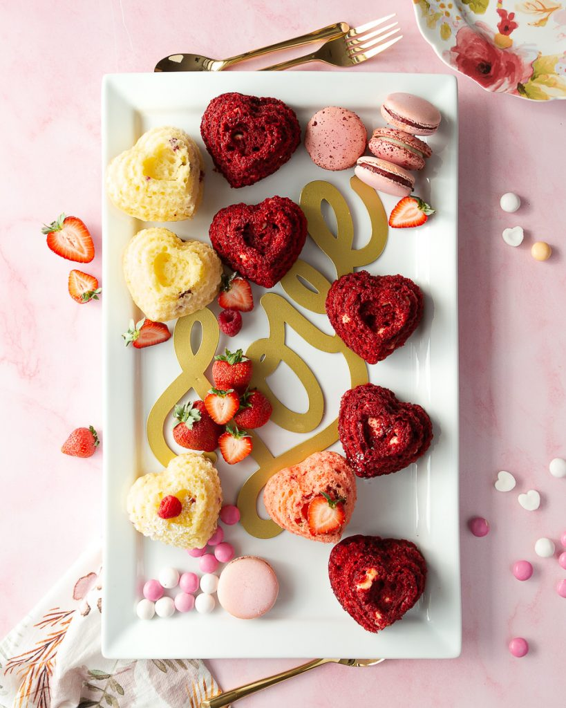A charcuterie platter of mini heart cakes, red velvet, strawberry, and raspberry.