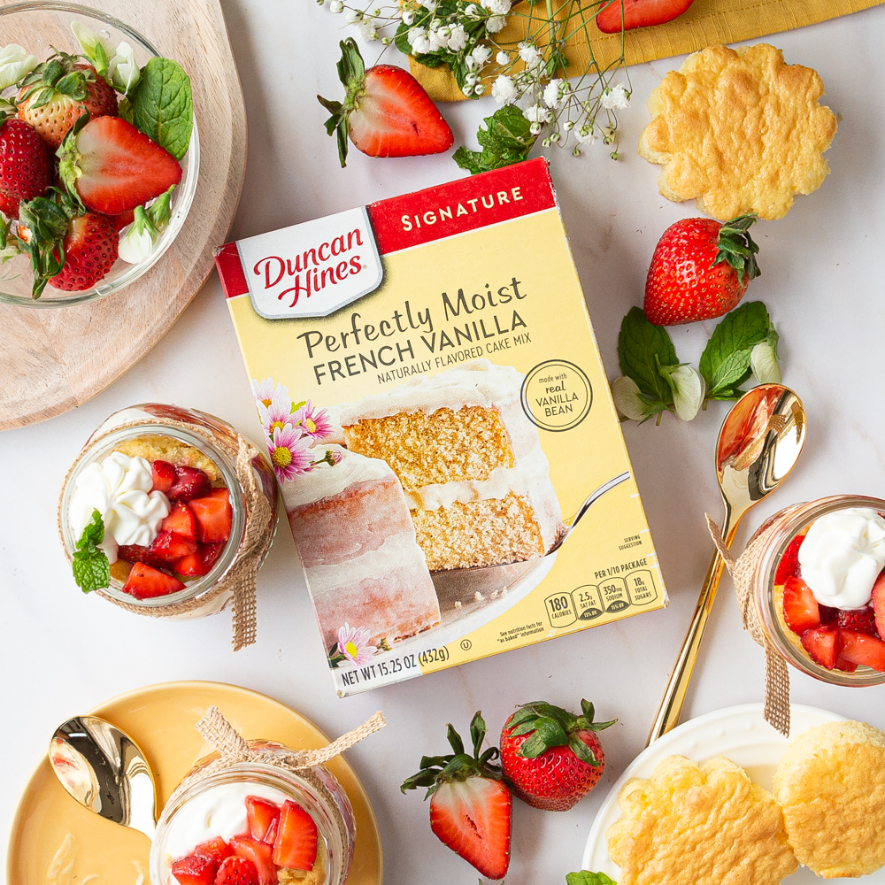 An overhead view of Duncan Hines French Vanilla Cake Mix with strawberries and whipped cream.
