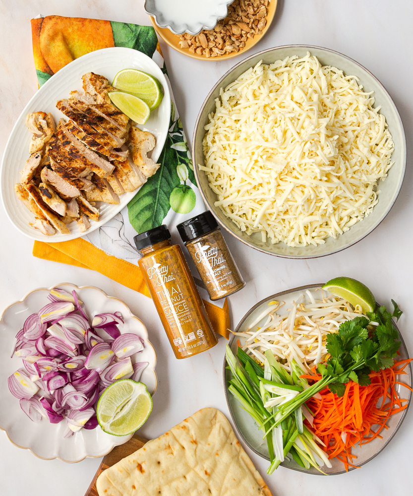 Ingredients for Thai Chicken Pizza: Flatbread, red onion, grilled chicken, peanut sauce, mozzarella cheese, carrots, green onion, bean sprouts, peanuts.
