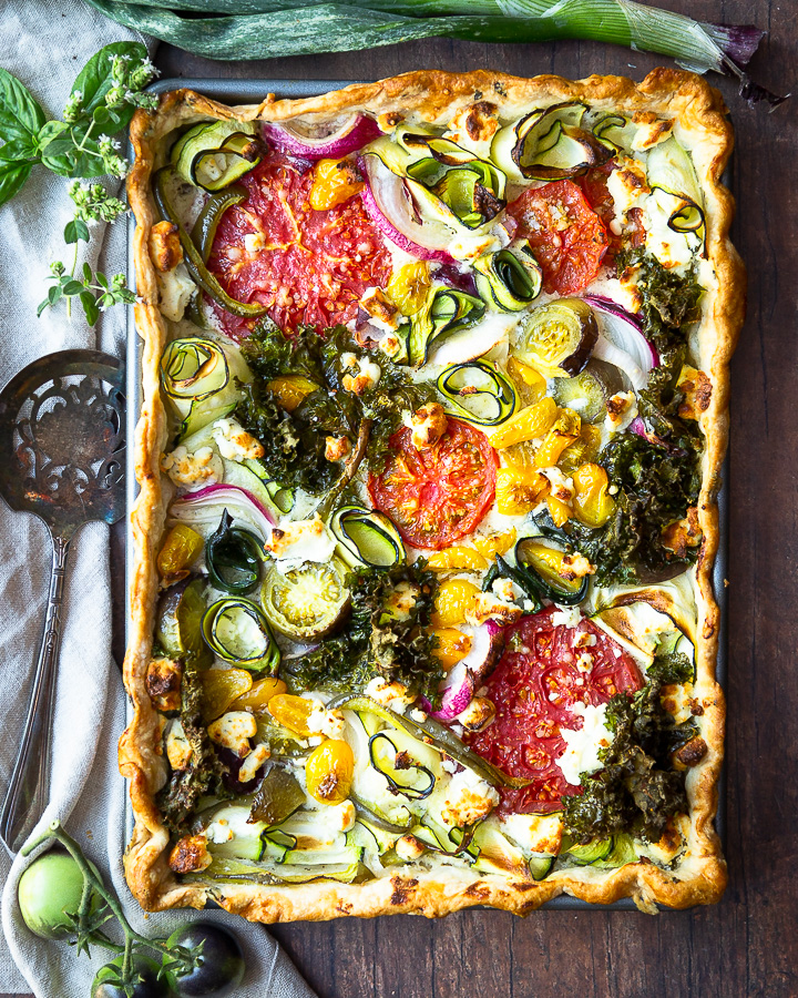 A savory garden veggie tart with tomatoes, zucchini, onion, and kale.