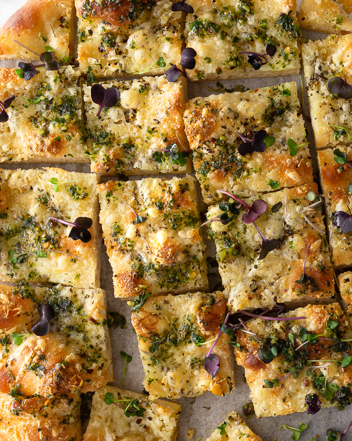 A flatbread pizza with parmesan cheese, herb oil, and basil microgreens.