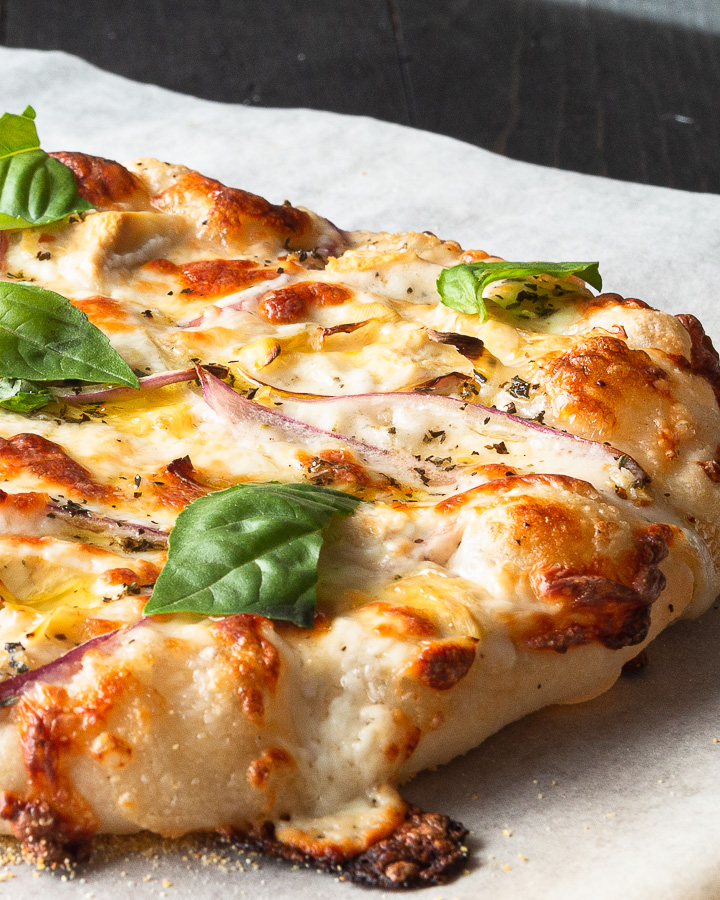 A white pizza using a master pizza dough recipe, Alfredo sauce, red onion, artichoke hearts, fresh basil leaves, and an herb oil to finish.